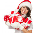 Woman holding gifts wearing red Santa hat — Stockfoto