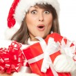 Girl in Santa hat, surprised by having received a lot of Xmas presents — Stock Photo