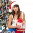 Stock Photo: Girl sitting near Christmas tree with many gifts