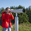 Stock Photo: Womlooking through sightseeing binoculars