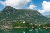 Mountains and village on the lake — Stock Photo