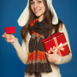 Winter woman with red gift box and credit card — Stock Photo