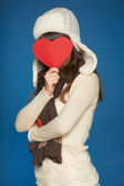 Winter girl holding heart shape in front of face — Stock Photo
