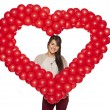 Stock Photo: Smiling womholding red balloon heart