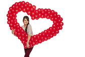 Smiling woman holding red balloon heart — Photo