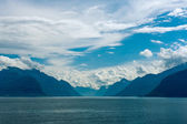 Fjord scene with hazy mountains and cloudy sky — Stock Photo