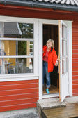 Woman looking out of a cabin door — Stok fotoğraf