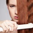Redheaded woman with hair straightening irons — Stock Photo