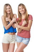 Happy two girl friends gesturing thumbs up — Stock Photo