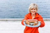 Happy woman giving cooked crab on plate — ストック写真