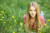 Spring girl lying on the field of dandelions — Stock Photo
