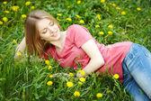 Chica de primavera en el campo de diente de león — Foto de Stock