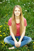 Female sitting on the field of dandelions — Foto Stock