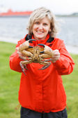 Happy woman showing alive crab outdoors — Foto Stock