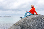 Woman sitting on stone against sea background — Stock Photo