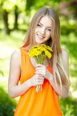 Spring girl with bunch of dandelions — Stock Photo