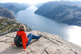 Woman sitting on Pulpit Rock / Preikestolen, Norway — Stock Photo