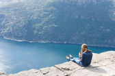 Woman sitting on Pulpit Rock / Preikestolen, Norway — Stock Photo