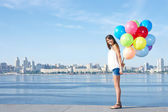 Happy young woman with colorful balloons — Stock Photo