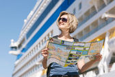 Woman with map, in front of cruise liner — Stok fotoğraf