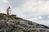 Lighthouse on a rocky cliff — Stock Photo
