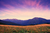 Mountain dawn with pink and violet clouds — Stock Photo