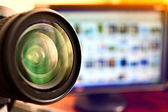 Lens of camera and computer monitor — Stock Photo