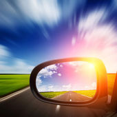 Car mirror with blue sky above road — Stock Photo