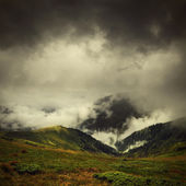 Dark clouds and fog over mountain valley — Stock Photo