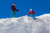 Girl skier with his mother on a steep slope in the mountains — Stockfoto