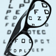 Eyeglasses over a blurry eye chart - Stock Photo