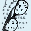 Stock Photo: Eyeglasses over blurry eye chart