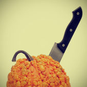 Warty pumpkin with a kitchen knife in it — Stock Photo