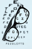 Eyeglasses over a blurry eye chart — Stock Photo