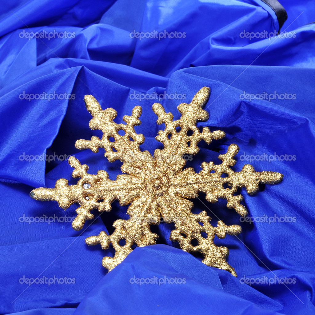 A golden christmas ornament with the shape of a snowflake on a blue fabric background — Stock fotografie #16417089