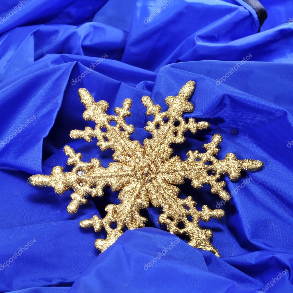 A golden christmas ornament with the shape of a snowflake on a blue fabric background — Lizenzfreies Foto #16417089