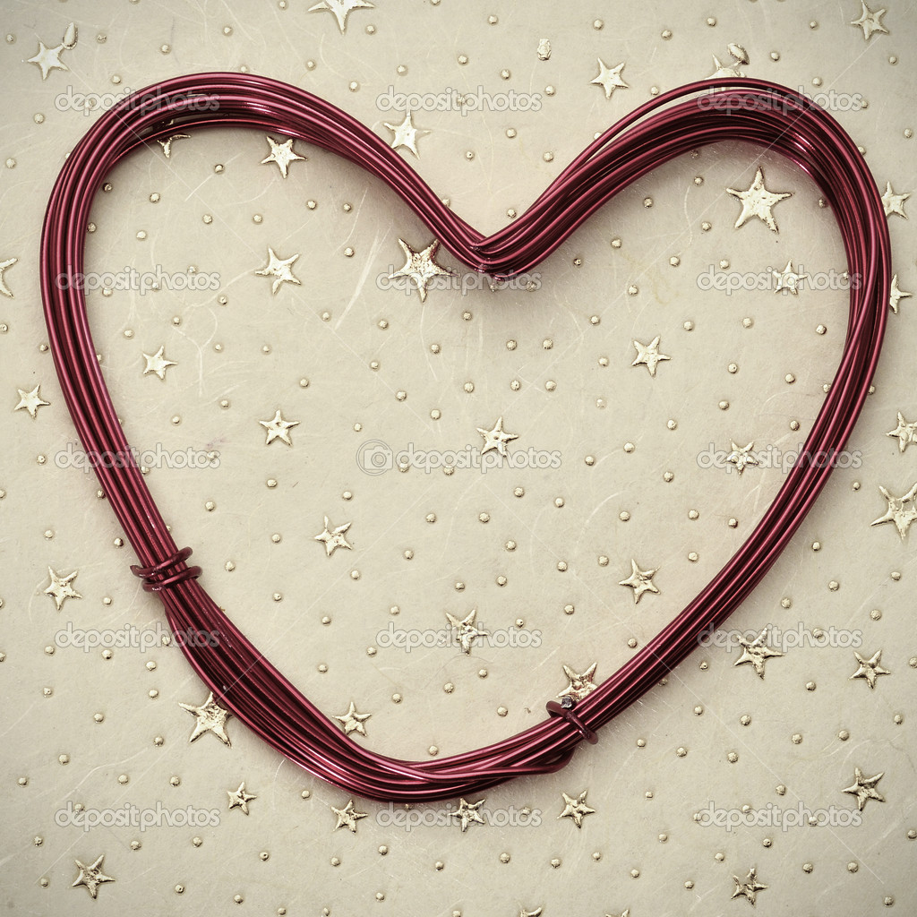Heart-shaped wire roll on a patterned background — Stock Photo #17166909
