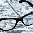Stock Photo: Dollar bills, eyeglasses and pen