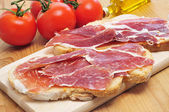 Sliced of bread with serrano ham served as tapas — Stock Photo