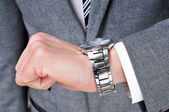 A man wearing a suit looking at his watch — Stock Photo