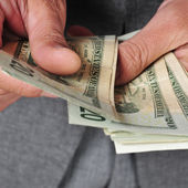 Man in suit with counting dollar bills — Stock Photo