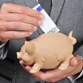 Man in suit introducing a euro bill in a piggy bank — Stock Photo