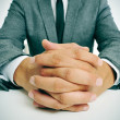 Man in suit with clasped hands — Stock Photo #30976175