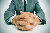 Man in suit with clasped hands — Stock Photo