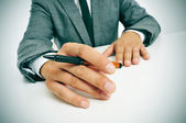 Man in suit with a pen in his hand — Stock Photo