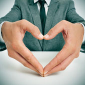 Man in suit forming a heart with his hands — Stock Photo