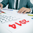 Stock Photo: Min suit with charts and 2014 calendar