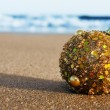 Christmas ball on the sand of a beach — Stock Photo