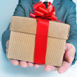Man in suit with a gift — Stock Photo