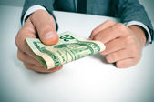 Man in suit with a wad of american dollar bills — Stock Photo